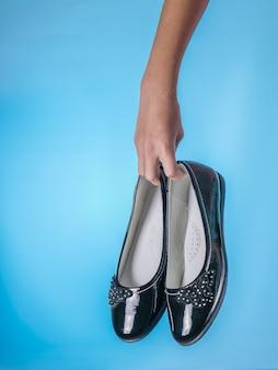 De rechterhand van het kind houdt modieuze damesschoenen op een blauwe achtergrond. stijlvolle en modieuze leren damesschoenen.