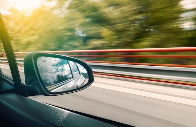 De reflectie in de achteruitkijkspiegel van de auto in beweging