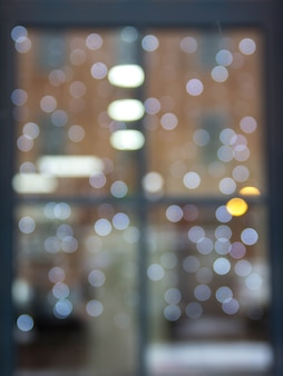 De reflectie in het venster met kerstverlichting