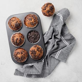 De regeling van chocoladeschilfersmuffins in bakseldienblad