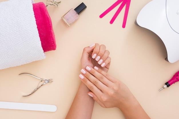 De regeling van manicure-elementen op beige achtergrond