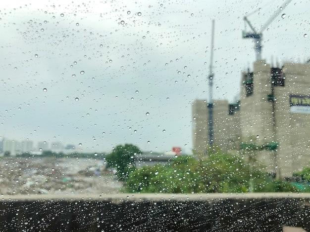 De regen op spiegelauto met de achtergrond van de bouwplaats.