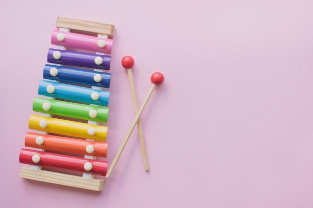 De regenboog kleurde houten xylofoon van het stuk speelgoed op roze bacground. speelgoed klokkenspel van metaal en hout. copyspace