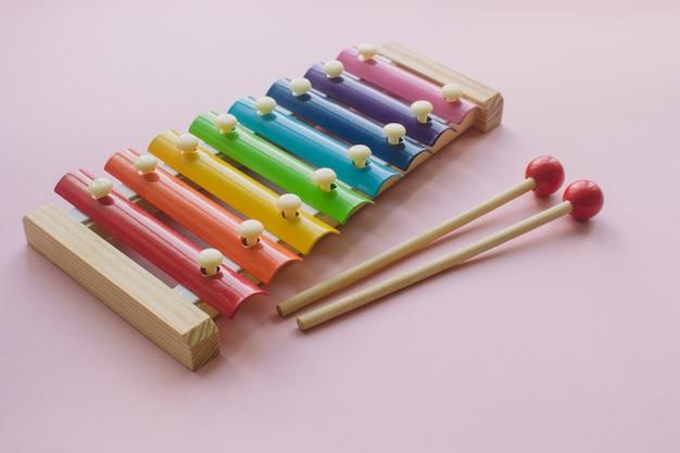 De regenboog kleurde houten xylofoon van het stuk speelgoed op roze bacground. speelgoed klokkenspel van metaal en hout