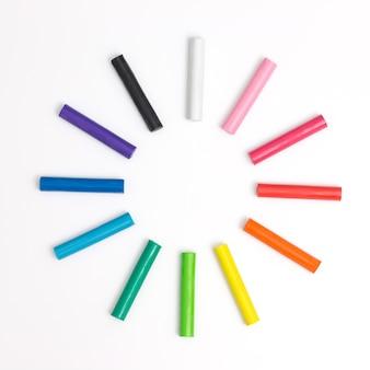 De regenboog kleurt plasticine speelt deeg modelleringsklei die over wit wordt geïsoleerd.