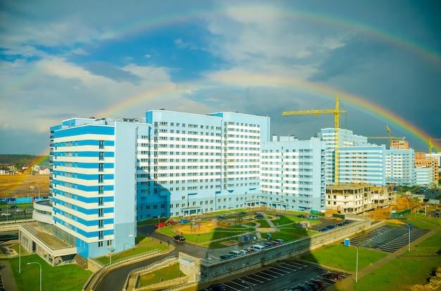 De regenboog strekt zich uit over de hoogbouw van de stad
