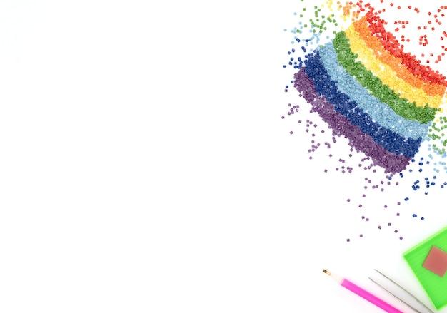 De regenboog van kleurrijke kristallen, pincet, stylusbakje voor diamantborduurwerk op witte achtergrond.
