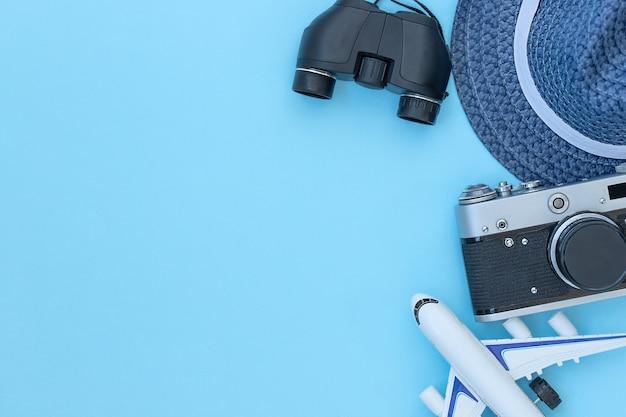 De reizende blauwe achtergrond met accessoires voor verrekijkers en vliegtuig met reishoed