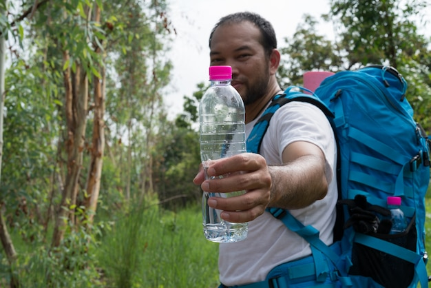 De reiziger die van azië een waterfles in openluchtbos op berglandschap houdt. adventures wandelen