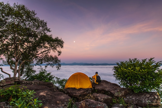 De reiziger en oranje tent op hoge berg en zee van mist.