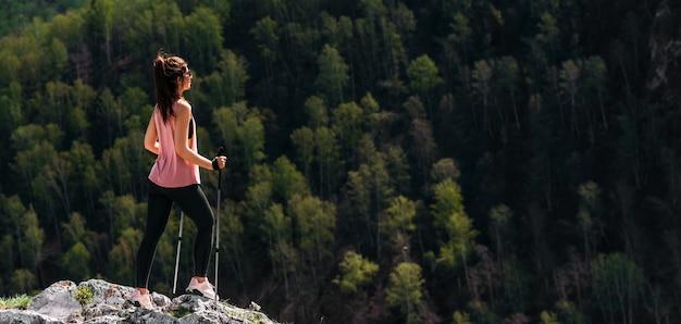 De reiziger is blij om de berg te beklimmen. wandelen in de bergen. bergsporten. de man op de top van de berg. bergtoerisme. een reis naar de bergen. ruimte kopiëren