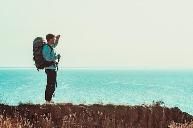 De reiziger met rugzak die op de bergtop boven de zee staat