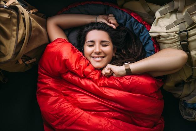 De reiziger rust in een slaapzak. rustconcept. een toerist rust in een tent. vrouw ontspannen in slaapzak. reizen, kampeerconcept, avontuur. gelukkig lachende vrouwelijke reiziger. de reiziger