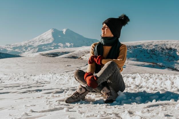 De reiziger zit in de winter op de weg met uitzicht op de vulkaan.