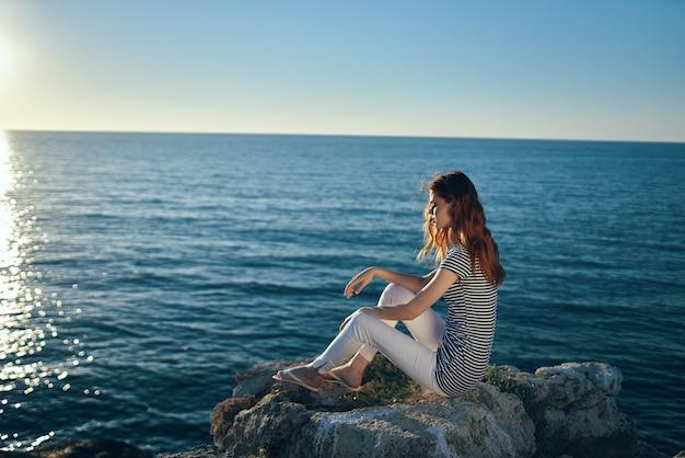 De reiziger zit op het strand vlakbij de zee in de bergen en zonsondergang