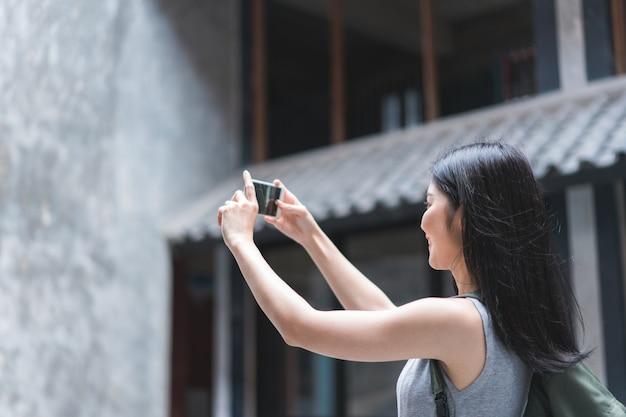 De reizigers aziatische vrouw die mobiele telefoon met behulp van voor neemt een beeld terwijl het besteden vakantiereis in peking, china