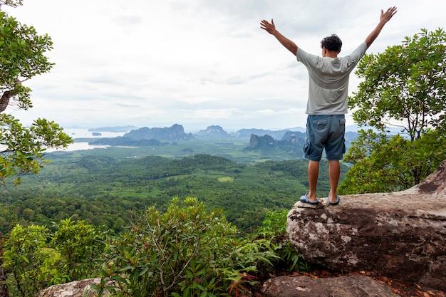 De reizigersmens die zich op grote steen bevinden die zijn hand tegenhouden en ziet landschapsmening in dragon crest-berg, het populaire avontuur van de oriëntatiepuntreis in krabi thailand