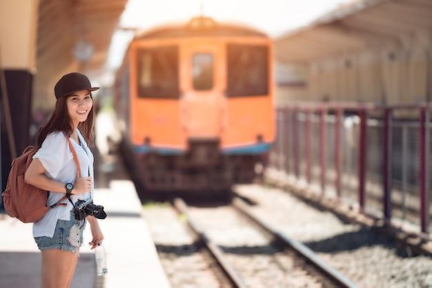 De reizigersvrouw die en wacht trein op spoorwegplatform wacht. uitstekende kleur