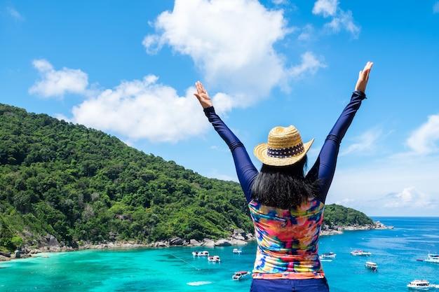 De reizigersvrouw met kleurrijk zwemmend kostuum hief wapens aan hemel op