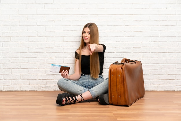 De reizigersvrouw met koffer en instapkaart richt vinger op u met een zekere uitdrukking