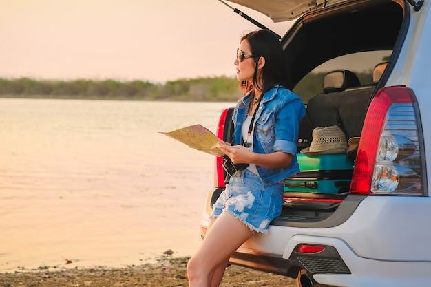 De reizigerszitting van azië op hatchbackauto en het bekijken kaart wanneer zonsondergang