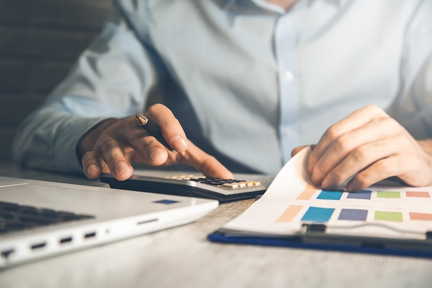 De rekenmachine van de mensenhand met grafiek op bureau