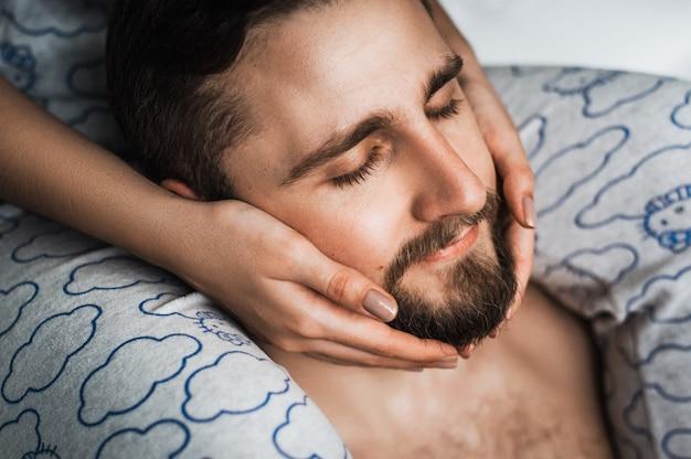 De relatie tussen een meisje en een jongen. raak mijn gezicht aan. handen op het gezicht. zorg voor een baard. huidverzorging. de handen van vrouwen op het gezicht van de man. mijn gezicht strelen