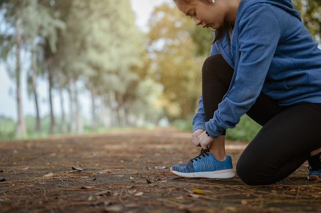 De rennende vrouw die veters van hardloopschoenen bindt voordat ze door de straat in het natuurpark jogt