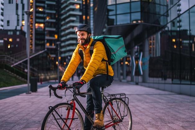 De renner van de voedselleveringsdienst die voedsel met fiets bezorgen