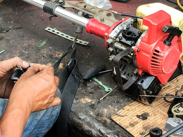 De reparateur bevestigt de grasmaaier met hulpmiddelen op de stoep