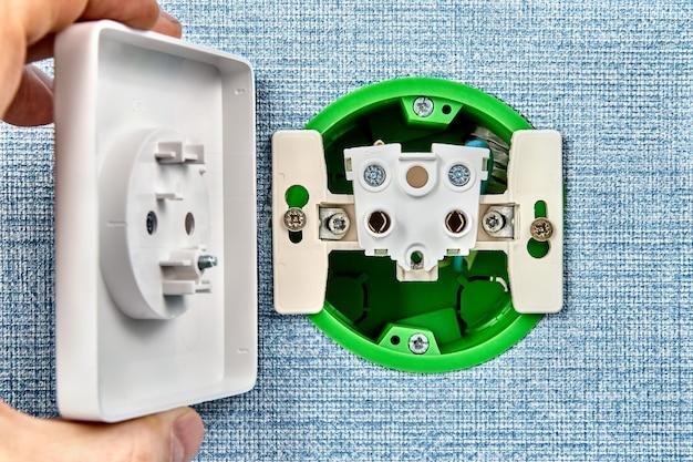 De reparateur bevestigt een losse wandhouder of een stopcontact van het elektrische systeem in huis.