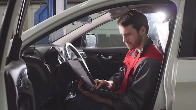 De reparateur, die gekleed is in een werkuniform, zit in het voertuig en controleert de versnellingsbak.