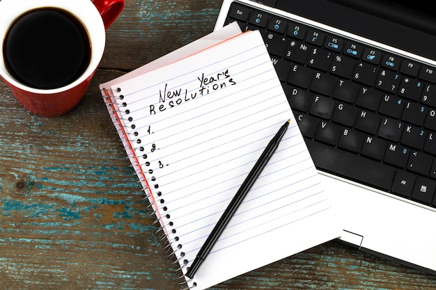 De resoluties van het nieuwe jaar geschreven op papier bovenop het toetsenbord van de laptop.