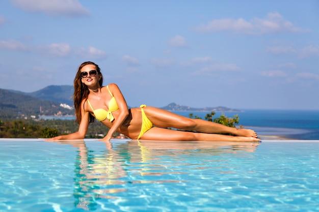 De rest van het eiland bij het zwembad. buitenmode van mooie, elegante, sexy vrouw met perfect gebruind lichaam, liggend in de zon en geniet van je vakantie. heldere, stijlvolle bikini en zonnebril dragen.
