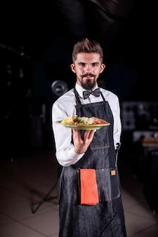 De restaurantmedewerker met bakkebaarden serveert een gekookt gerecht