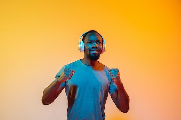 De retro wave of synth wave portret van een jonge gelukkig ernstige afrikaanse man in de studio.