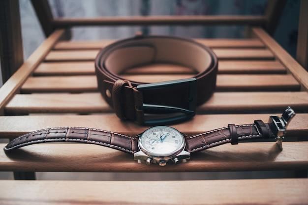 De riem en de horloges van bruidegomtoebehoren op houten achtergrond