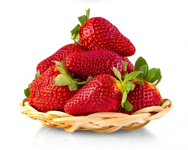 De rieten bruine mand met aardbeien die op witte achtergrond worden geïsoleerd. rijpe aardbeien close-up.