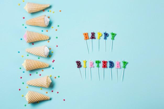 De rij van aalaw in de wafelkegel met bestrooit dichtbij de gelukkige verjaardagskaarsen op blauwe achtergrond