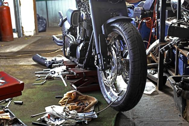 De rij van schroeven en moersleutelhulpmiddelen op een vloer in workshop herstelde dichtbij oude fiets of motorfietsmotor. industriële scène met apparatuur