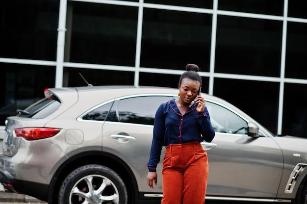 De rijke afrikaanse bedrijfsvrouw in oranje broek en blauw overhemd spreekt op mobiele telefoon