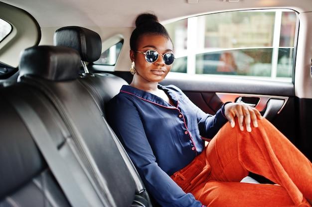 De rijke afrikaanse bedrijfsvrouw op zonnebril zit bij suv auto met zwarte leerzetels