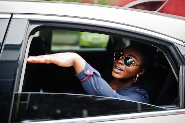 De rijke afrikaanse bedrijfsvrouw op zonnebril zit bij suvauto en toont hand van venster
