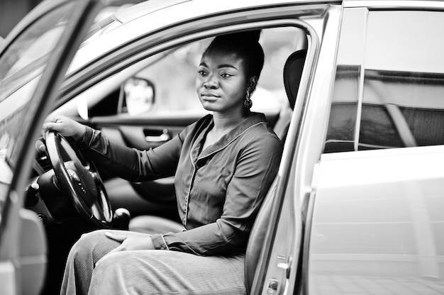 De rijke afrikaanse bedrijfsvrouw zit op bestuurderszetel bij zilveren suv auto met geopende deur