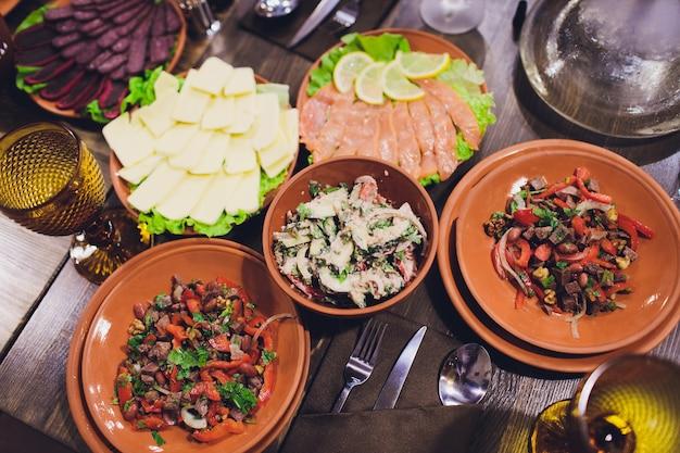 De rijkelijk gedekte tafelgerechten van de georgische keuken, veel heerlijk eten, wijn, fruit en geroosterd vlees.