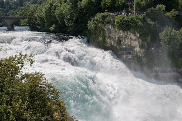 De rijnwaterval is de grootste waterval van europa in schaffhausen, zwitserland. zomerlandschap, zonneschijn, blauwe lucht en zonnige dag