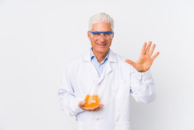 De rijpe chemische mens isoleerde het glimlachen vrolijk tonend nummer vijf met vingers.