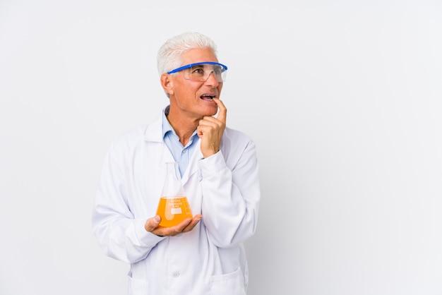 De rijpe chemische mens ontspande het denken over iets bekijkend een lege ruimte.