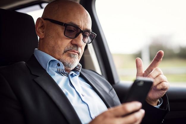 De rijpe ernstige zakenman zit in zijn auto en kijkt nieuwsgierig in zijn telefoon.