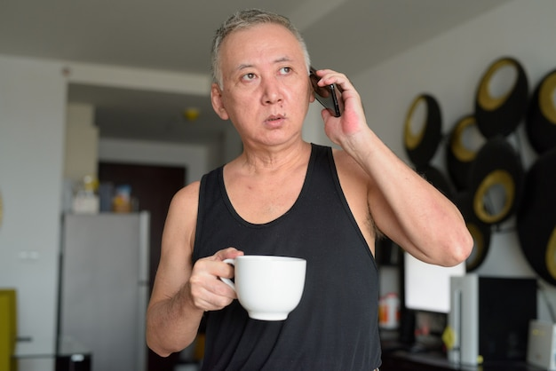 De rijpe japanse koffie van de mensenholding terwijl thuis het spreken op de telefoon